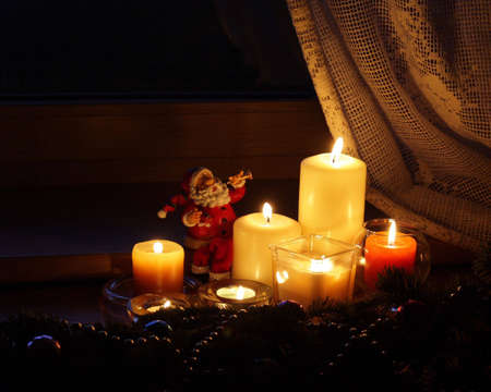 celeb: Candles  and Santa Claus with Christmas decorations in dark interior