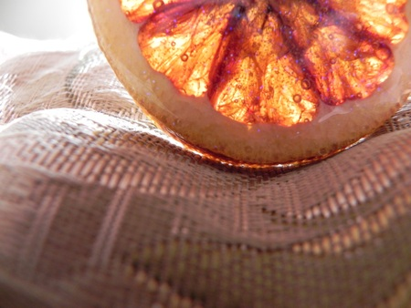 bedspread: Enamel dried blood orange pin on bedspread with natural sunlight shining through  Lifestyle concept  new age, healing; new day or dawn; waking up refreshed, revitalized or energized; visualizations