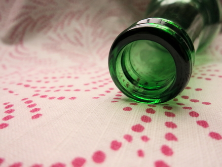 Soft green and pink hues of bottle on dotted cotton napkin.