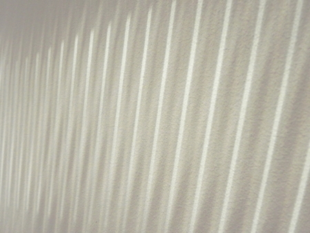 gritty: Light shining through vertical blinds against gritty off white wall.