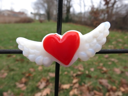 Red heart with wings glass magnet centered on metal fence, with grass in backdrop.