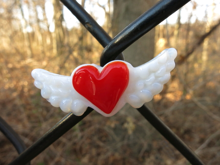 glass fence: Glass red heart with wings magnet centered on chain link fence. Stock Photo