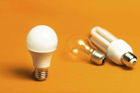 bombilla: Tungsteno, fluorescente y bombillas LED aislados sobre un fondo naranja Foto de archivo