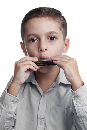 Kid playing harmonica on white background Stock Photo