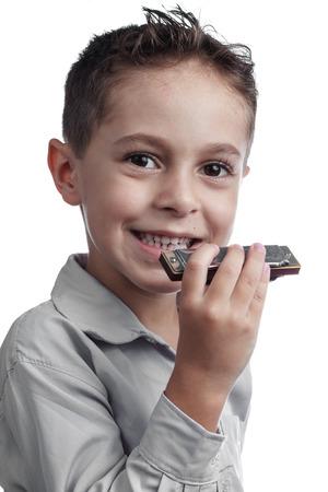 ide: Smiling kid holding harmonica on white background