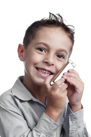 ide: Smiling kid holding harmonica on white background