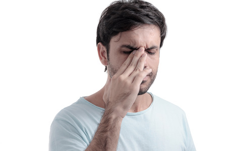 headache pain: Sinus pain, sinus pressure, sinusitis. Sad man holding his nose because sinus pain Stock Photo