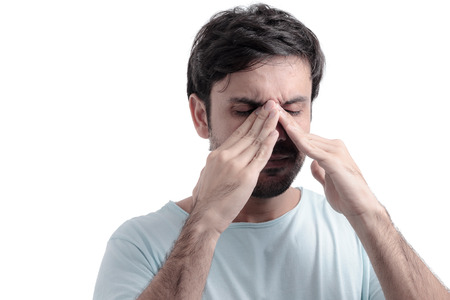 head pain: Sinus pain, sinus pressure, sinusitis. Sad man holding his nose because sinus pain Stock Photo