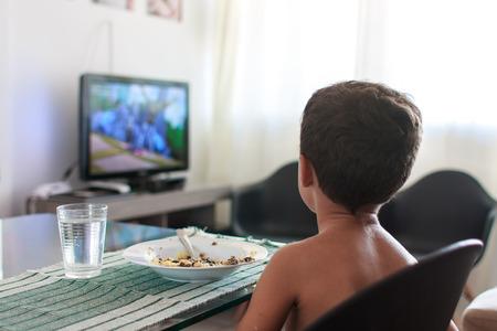 Bambino distratto guardare la tv pranzo mangiare Archivio Fotografico - 50847037