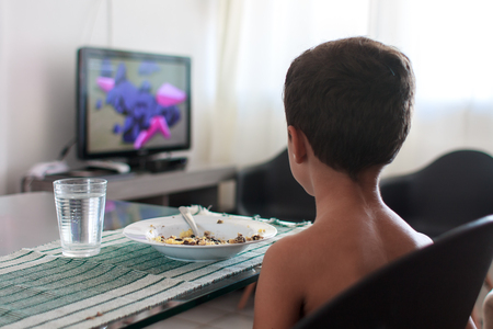 Child distracted watching tv eating lunch