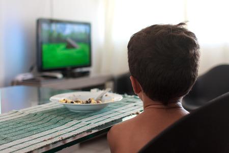 Bambino distratto guardare la tv pranzo mangiare Archivio Fotografico - 50847044