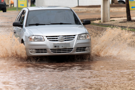 hydroplaning: silver car crossing flooded street after rains Stock Photo