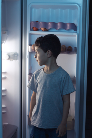 merienda: Niño que mira en el refrigerador en el medio de la noche