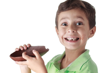 paschal: Little boy eating chocolate easter egg on white background