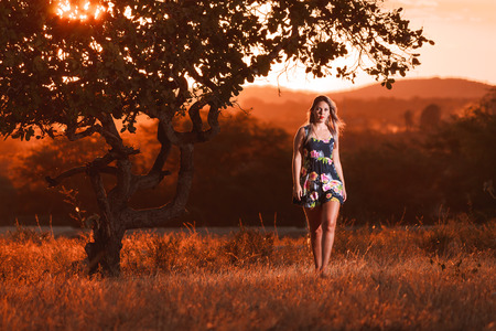 beautiful young woman walks in the field at sunset