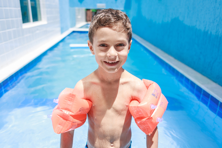 armbands: Sweet little boy boy in swimsuit with arm float in the pool