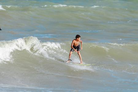 ber: Cabedelo, Paraiba, Brazil - September 18, 2016 - Child surfs in Intermares Beach