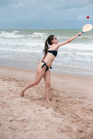 brazil beach swimsuit: Beautiful young brunette playing beach tennis in Brazil Stock Photo