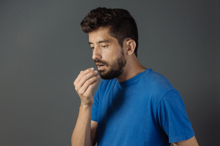 Bad breath. Halitosis concept. Young man checking his breath with his hand. Stock Photo