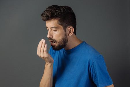 Slechte adem. Halitosis concept. Jonge man het controleren van zijn adem met zijn hand.