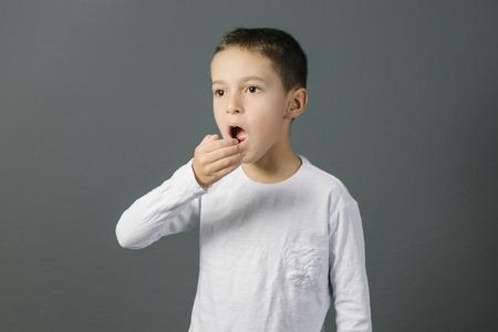 구취. 구내 증 개념. 그의 손으로 그의 호흡을 검사하는 아이.