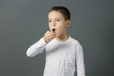 disgusted: Bad breath. Halitosis concept. Child checking his breath with his hand.
