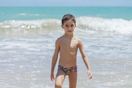 Six year old boy having fun on tropical beach in sunny day