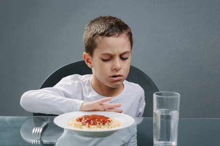 Portrait of child with no appetite in front of the meal. Concept of loss of appetite Stock Photo