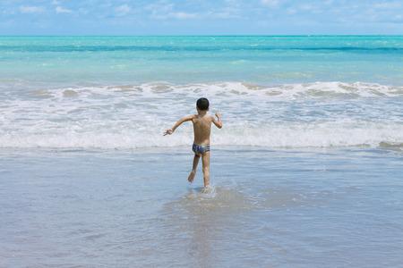 brazil beach swimsuit: Six year old boy having fun on tropical beach in sunny day