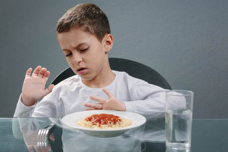 no food: Portrait of child with no appetite in front of the meal. Concept of loss of appetite Stock Photo