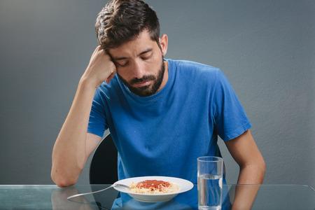食事の前に食欲を持たない男の肖像画。食欲の損失の概念 写真素材