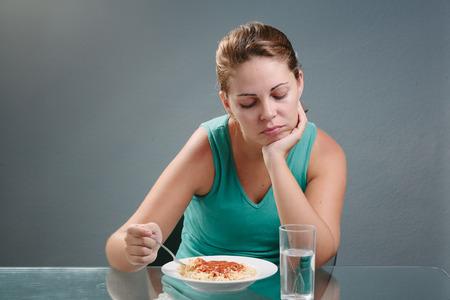 Portret van vrouw met geen trek in de voorkant van de maaltijd. Concept van het verlies van eetlust