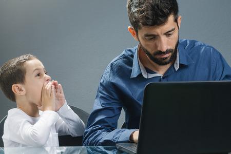 Vader op de laptop negeren zoon terwijl het kind probeert zijn aandacht te trekken.