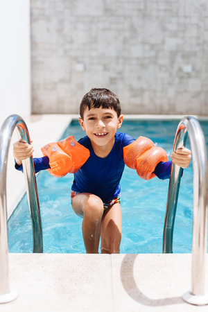 armbands: Sweet little boy in swimsuit with arm float in the pool