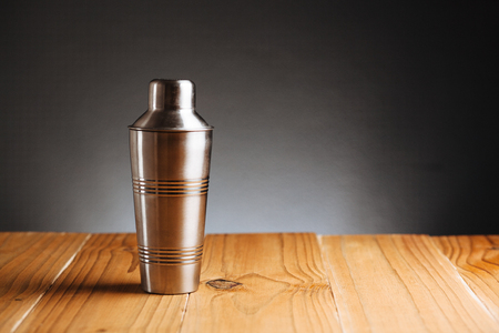 Cocktail shaker on wooden table on dark background