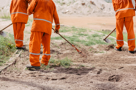 근로자는 괭이를 사용하여 잡초를 제거합니다. 인도의 건설