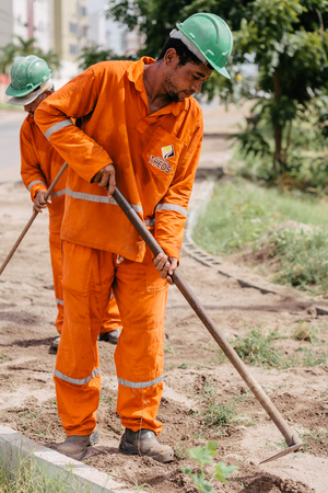 Cabedelo, Paraiba, Brazil - March 31, 2017 - Worker using hoe to remove weeds Editorial