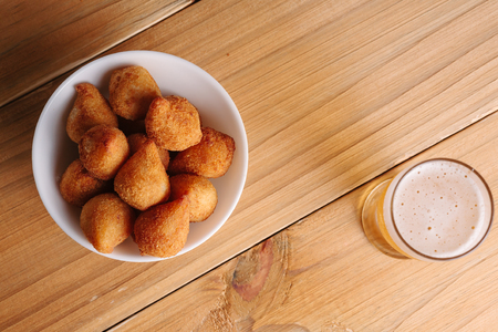 Brazilian snack coxinha and beer on wood table
