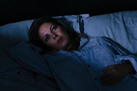 gente durmiendo: trastorno del sueño, insomnio. La mujer rubia joven tumbado en la cama despierto
