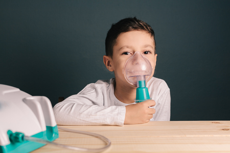 Beautiful sick boy inhalation therapy by the mask of inhaler. Image of a cute kid with respiratory problem or asthma. View of nebulizer with smoke from oxygen mask.