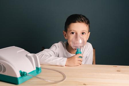 Bella terapia di inalazione di ragazzo malato con la maschera di inalatore. Immagine di un ragazzo sveglio con problemi respiratori o asma. Vista del nebulizzatore con fumo dalla maschera di ossigeno. Archivio Fotografico - 76987046