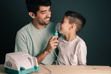 Portrait of father and son using domestic inhaler  nebulizer