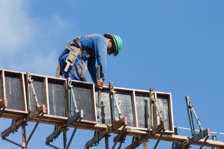 Cabedelo, Paraiba, Brasil - 4 de mayo de 2017 - Trabajador de la construcción trabajando en la parte superior del sitio de construcción en un día soleado Editorial