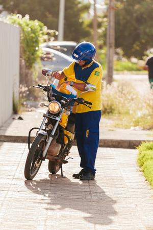 Cabedelo, Paraiba, Brasile - 17 maggio 2017 - Postino dell'impresa Brasileira de Correios e Telegrafos (inglese: Brazilian Post e Telegraph Corporation), noto anche come Correios, che consegna corrispondenza in motocicletta Archivio Fotografico - 78381693