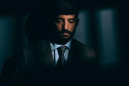 political prisoner: Businessman or political prisoner in dark cell. Concept of white collar crime