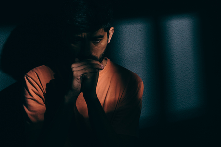 jail: Prisoner man in dark cell depressed or praying Stock Photo