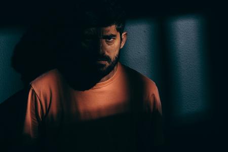 Prisoner angry man in dark cell
