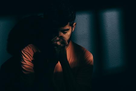 落ち込んで暗いセルまたは祈りの囚人男 写真素材