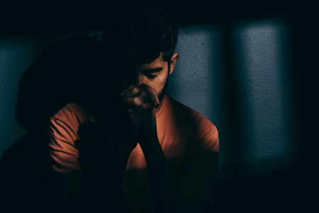 Prisoner man in dark cell depressed or praying Stock Photo