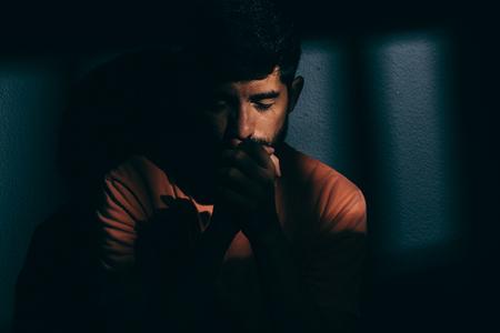 Prisoner man in dark cell depressed or praying Stock fotó